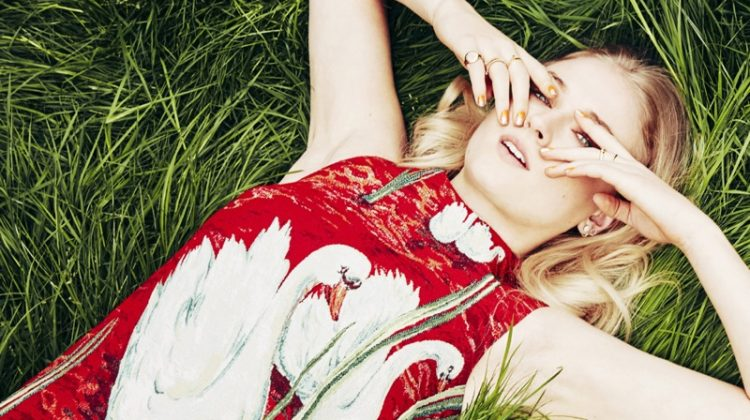 Actress Sophie Turner poses in the grass wearing a swan print dress