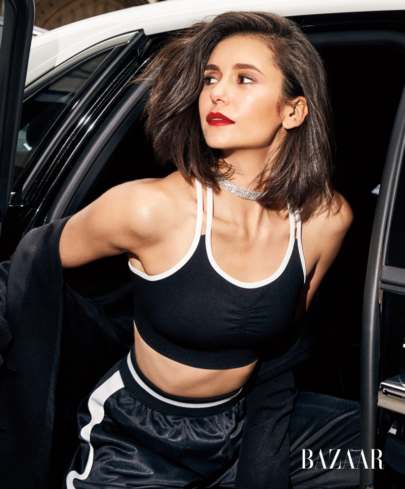 Nina Dobrev poses in DKNY jacket and DKNY Sport sport bra and Casato jewelry