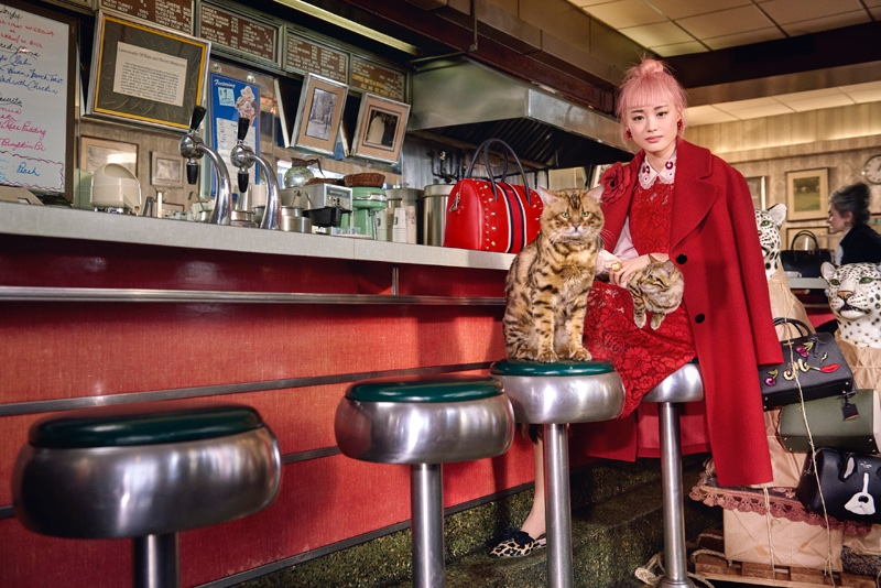 Fernanda Ly poses in a New York diner wearing a red jacket for Kate Spade's fall-winter 2017 ad campaign