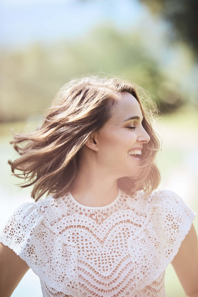 All smiles, Natalie Portman wears a white dress