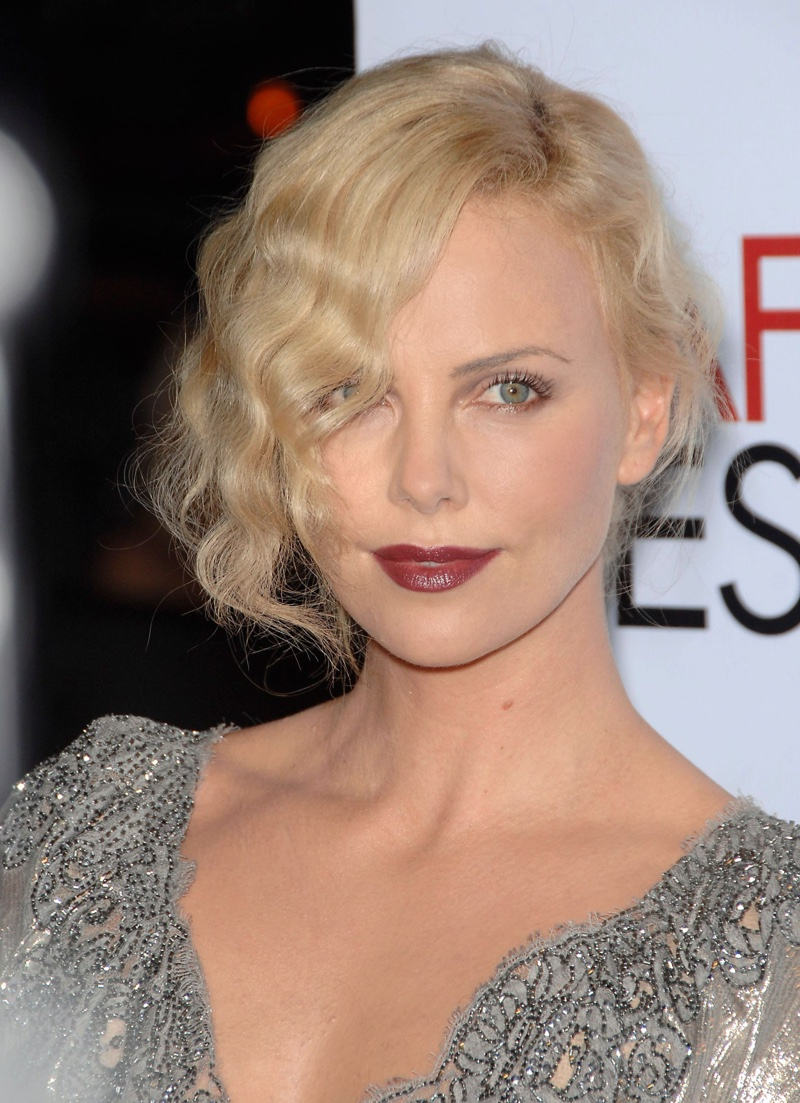 Actress Charlize Theron wears her hair in tousled finger waves in a modern, 1920s inspired updo.