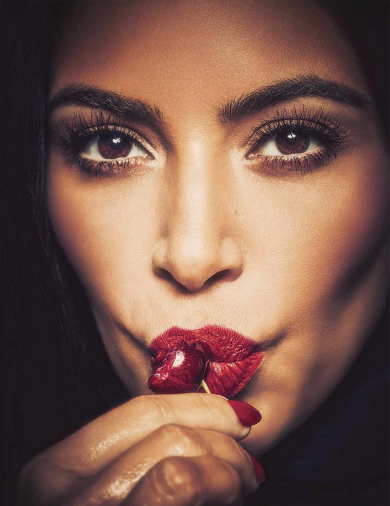 Kim Kardashian poses in bold scarlet lipstick with matching manicure