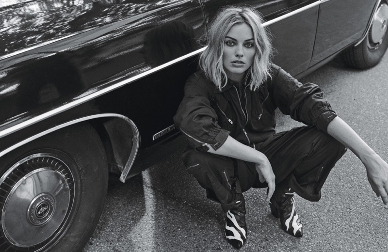 Photographed in black and white, Margot Robbie wears Nili Lotan jumpsuit, Gucci shirt and Louis Vuitton boots