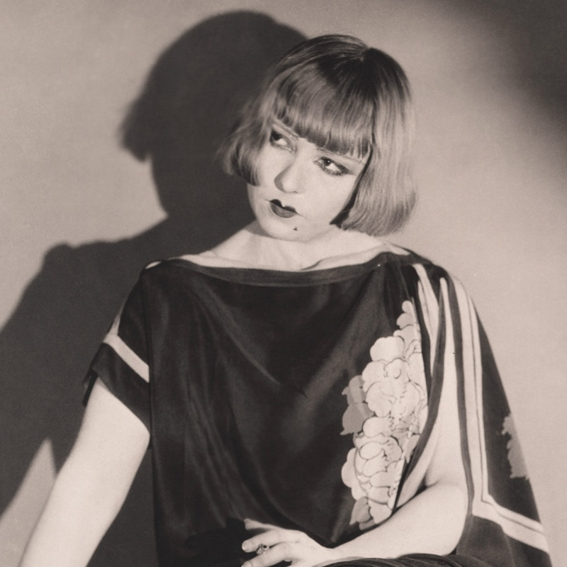 The most famous hairstyle of the 1920s was the bob cut. Here it is with chic bangs.