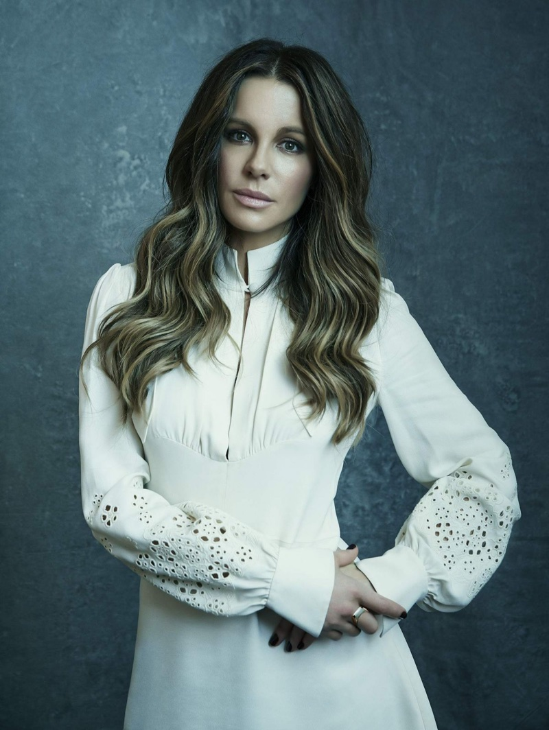 Actress Kate Beckinsale poses in white dress with eyelet sleeves