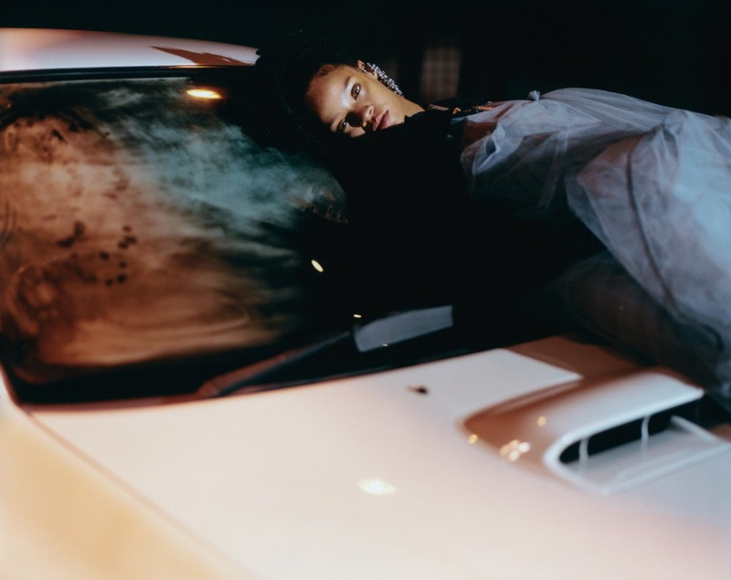 Lounging on a car, Rihanna wears Unravel bolero bomber jacket, Molly Goddard tulle dress and Mulberry earrings