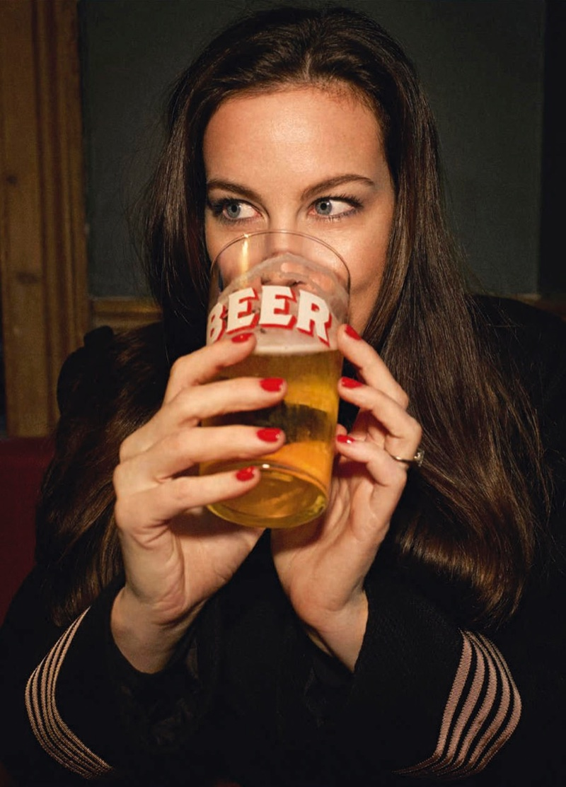 Taking a drink of beer, Liv Tyler shows off a red manicure