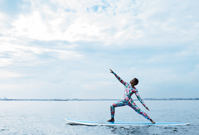 Actress Lupita Nyong'o poses on a paddleboard wearing a Dolce & Gabbana jumpsuit