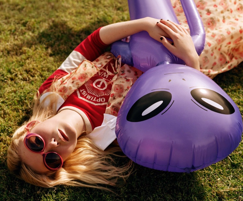 Posing on grass, Elle Fanning holds on to a purple alien toy