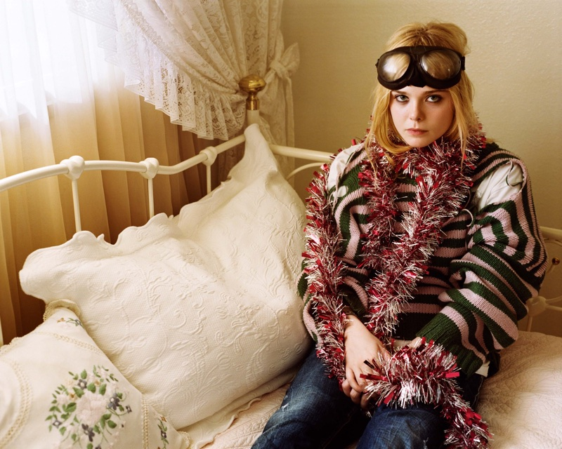 Posing in bed, Elle Fanning wears a whimsical look with a striped sweater
