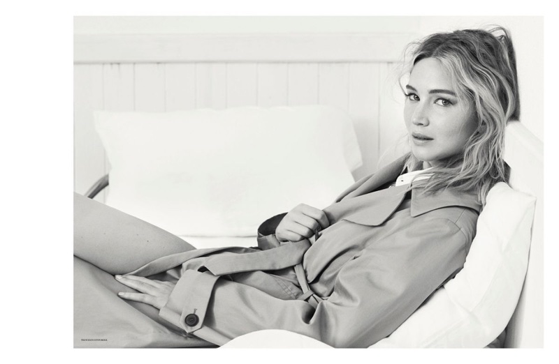 Photographed in black and white, Jennifer Lawrence wears Dior trench coat and shirt