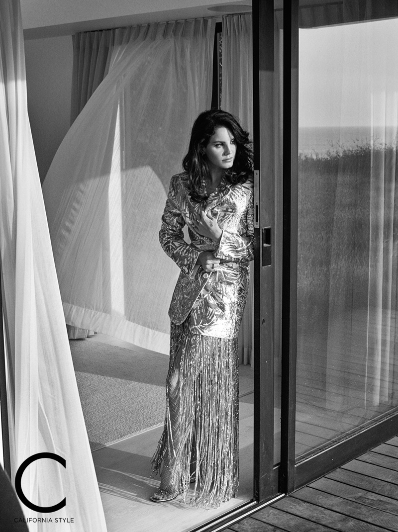 Singer Lana Del Rey poses in Michael Kors Collection jacket, Paco Rabanne skirt and Giuseppe Zanotti sandals