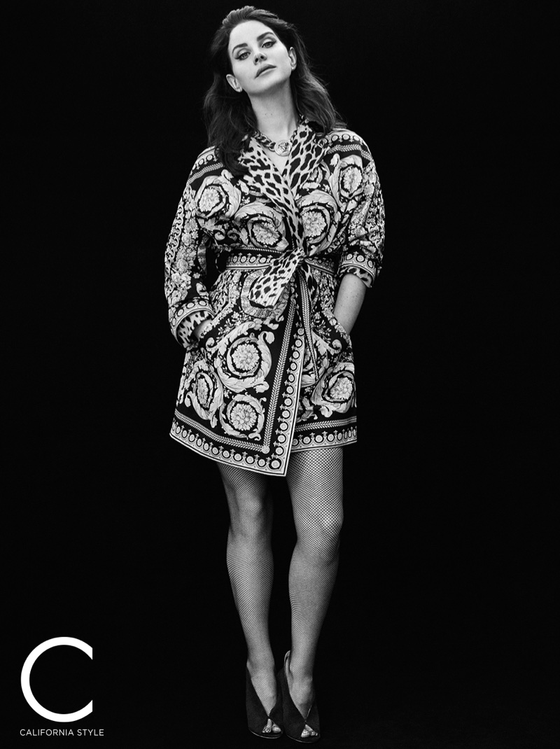Photographed in black and white, Lana Del Rey wears Versace trench coat and choker necklace with Jimmy Choo heels