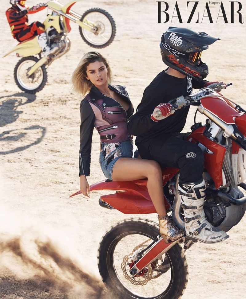 Posing on the back of a bike, Selena Gomez wears Coach 1941 jacket, shorts and booties