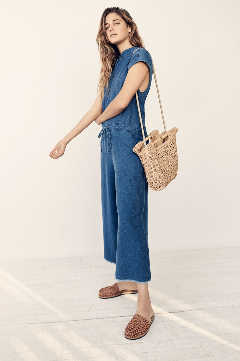 Ally Walsh wears NSF Carmina Jumpsuit and Free People Dreamland Straw Clutch