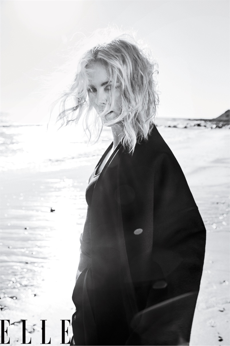 Photographed in black and white, Charlize Theron wears Valentino Haute Couture coat and pants