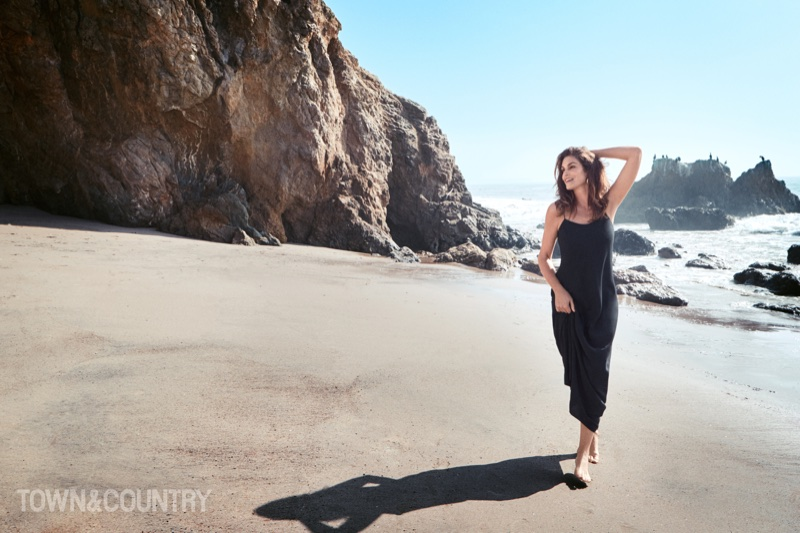 Posing on the beach, Cindy Crawford wears a black dress