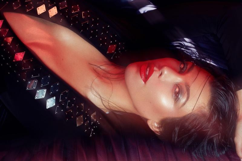 Wearing red lipstick, Kourtney Kardashian poses in Mugler bodysuit