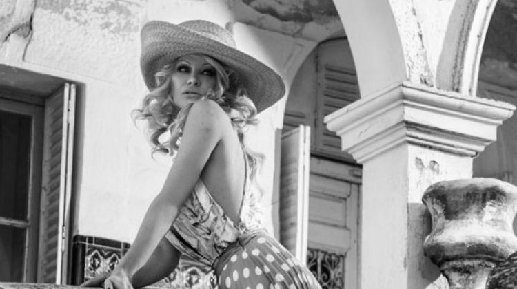 Actress Pamela Anderson poses in printed top and polka dot print skirt