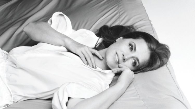 Photographed in black and white, Amy Adams poses in white blouse