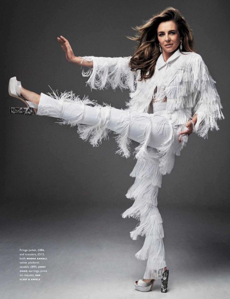 Kicking up her heels, Elizabeth Hurley wears Norma Kamali fringe jacket and pants with Jimmy Choo platforms