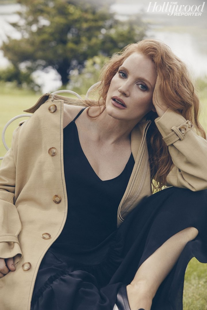 Actress Jessica Chastain poses in black dress and camel coat