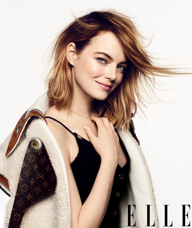 Actress Emma Stone poses in Louis Vuitton coat and dress with Cartier necklace