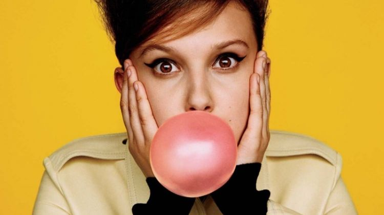 Posing with bubblegum, Millie Bobby Brown wears Calvin Klein dress and turtleneck