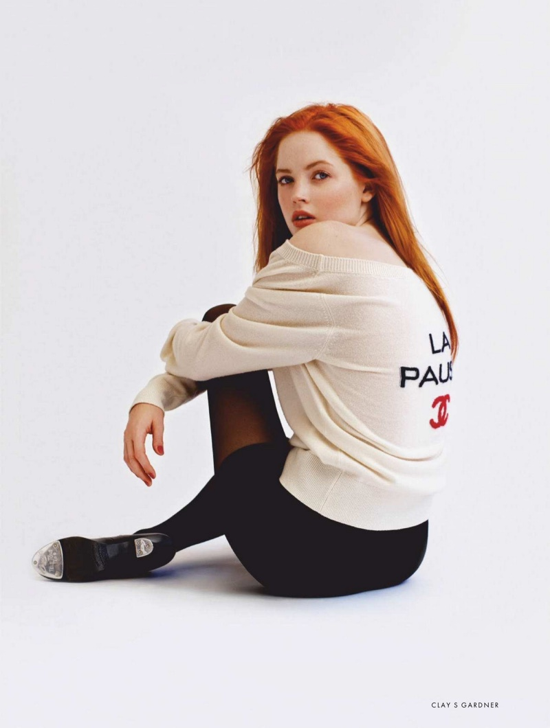 Actress Ellie Bamber wears Chanel sweater and earrings with Capezio tights and shorts