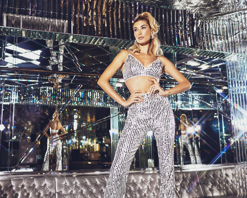 Hailey Baldwin wears PrettyLittleThing Silver Sequin Strappy Bralet $30 and Silver Sequin High Waisted Flare Trousers $68