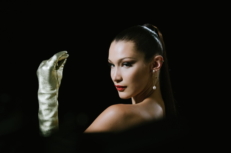 Wearing gloves, Bella Hadid appears on set of Dior makeup shoot