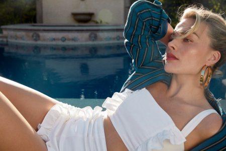 Posing poolside, Margot Robbie wears a white bikini set and blue coverup