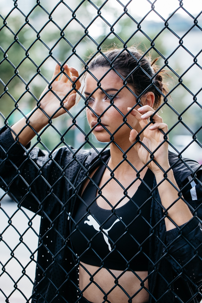 Posing behind the fence, Adriana Lima appears in PUMA x Maybelline advertisement