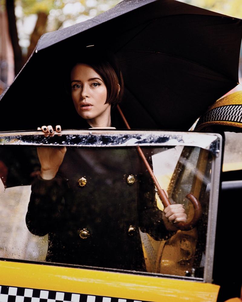 Posing next to a cab, Claire Foy wears Prada coat and headband