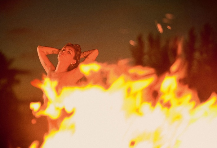 Through the fire, Miley Cyrus goes topless
