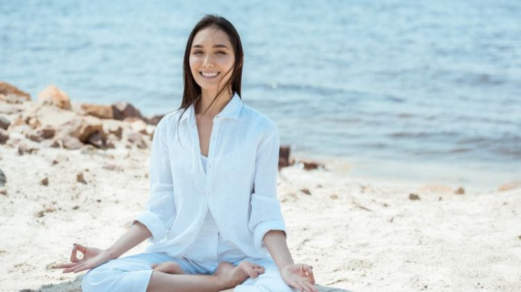 Woman in Yoga Pose Wearing White Outfit at Beach