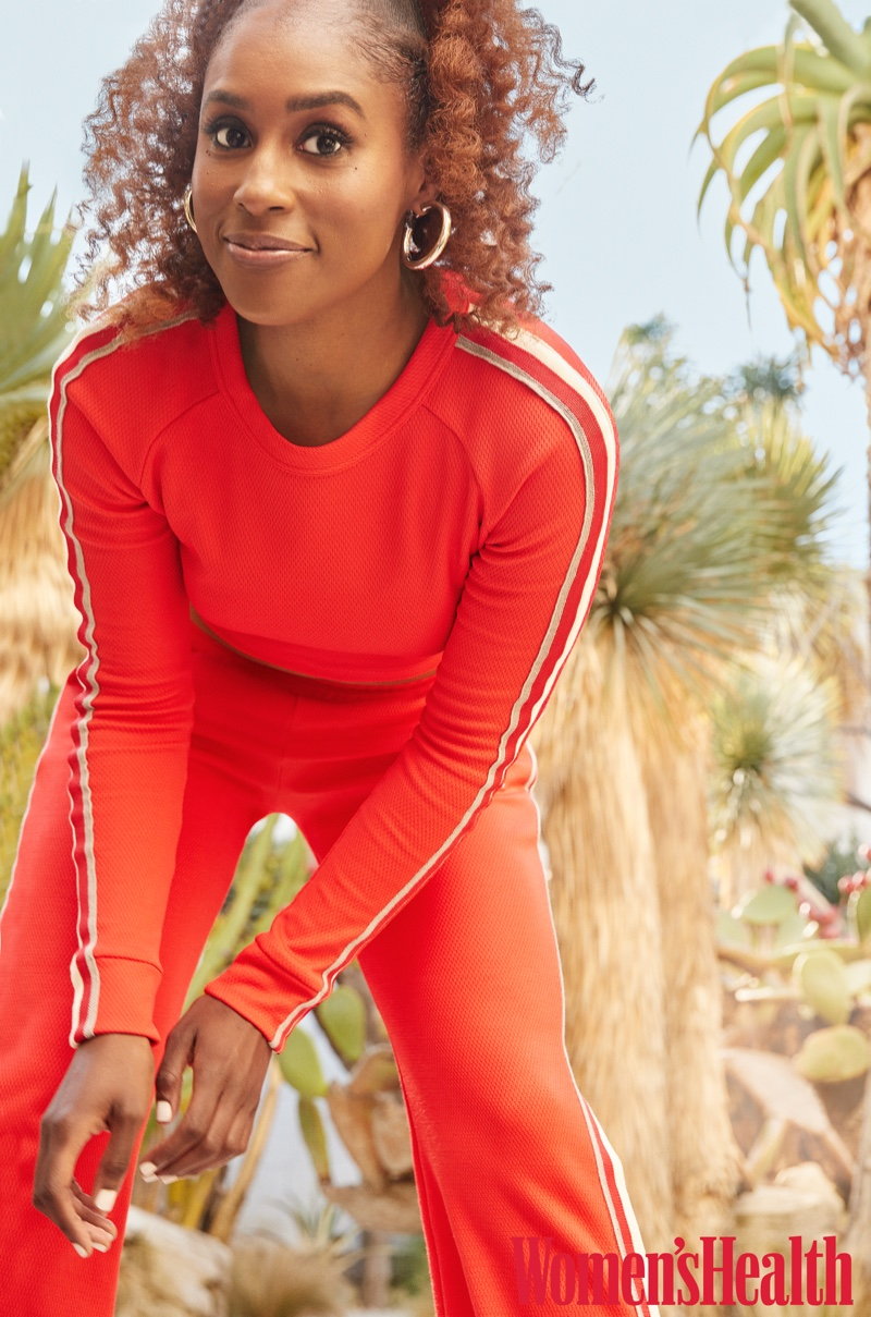 Dressed in red, Issa Rae wears Twenty Montreal top and pants with Jennifer Fisher earrings