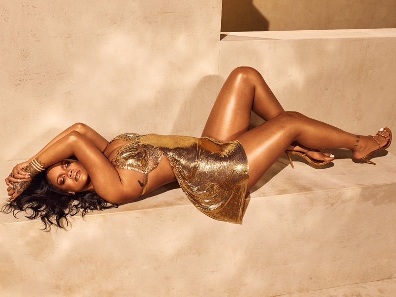 Singer Rihanna shines in a gold dress for Fenty Beauty Body Lava campaign