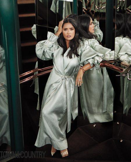 Salma Hayek poses in Peter Pilotto trench coat, Pomellato jewelry and Gucci sandals