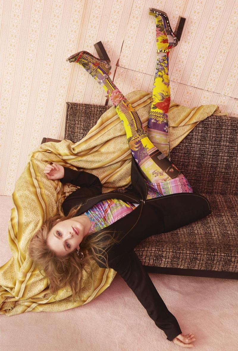 Taylor Swift models Mugler jacket, Versace dress and tights with Balenciaga sandals