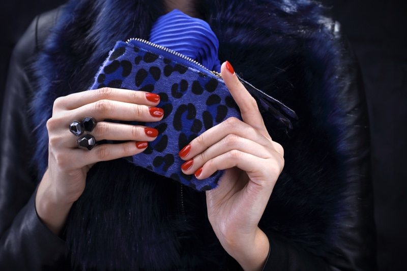 Woman with Blue Leopard Print Wallet and Red Nails