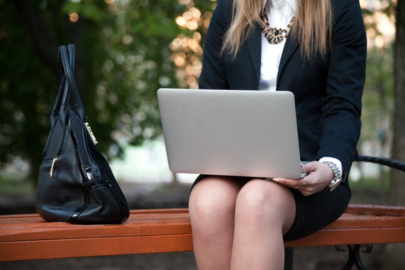 Woman in Business Outfit with Laptop and Bag