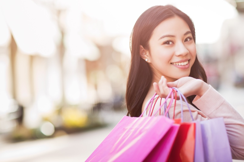 Asian Woman Smiling with Shopping Bags