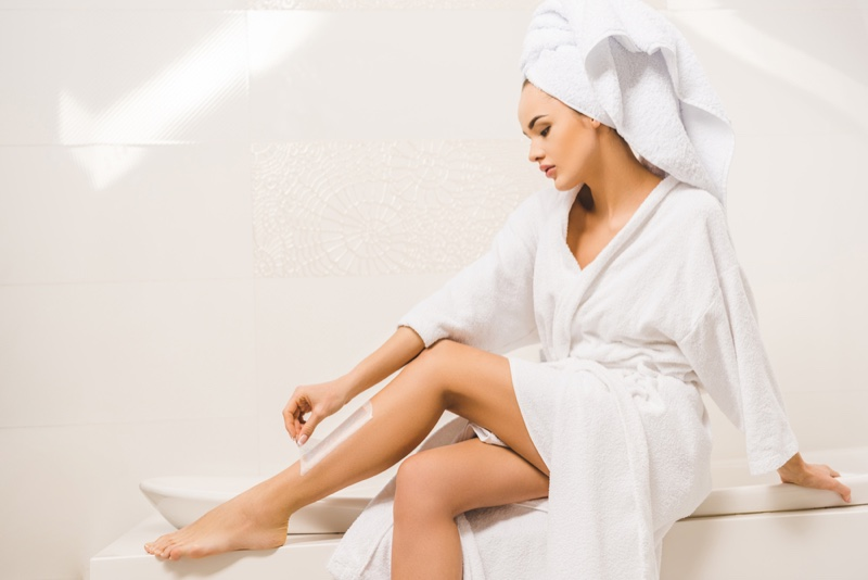 Woman Waxing Legs in a Robe