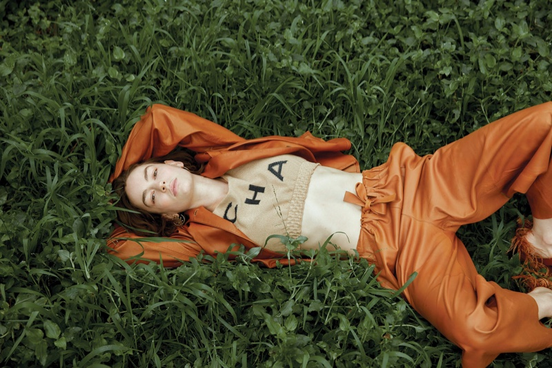 Surrounded by grass, Brigette Lundy-Paine wears a Chanel top with leather separates