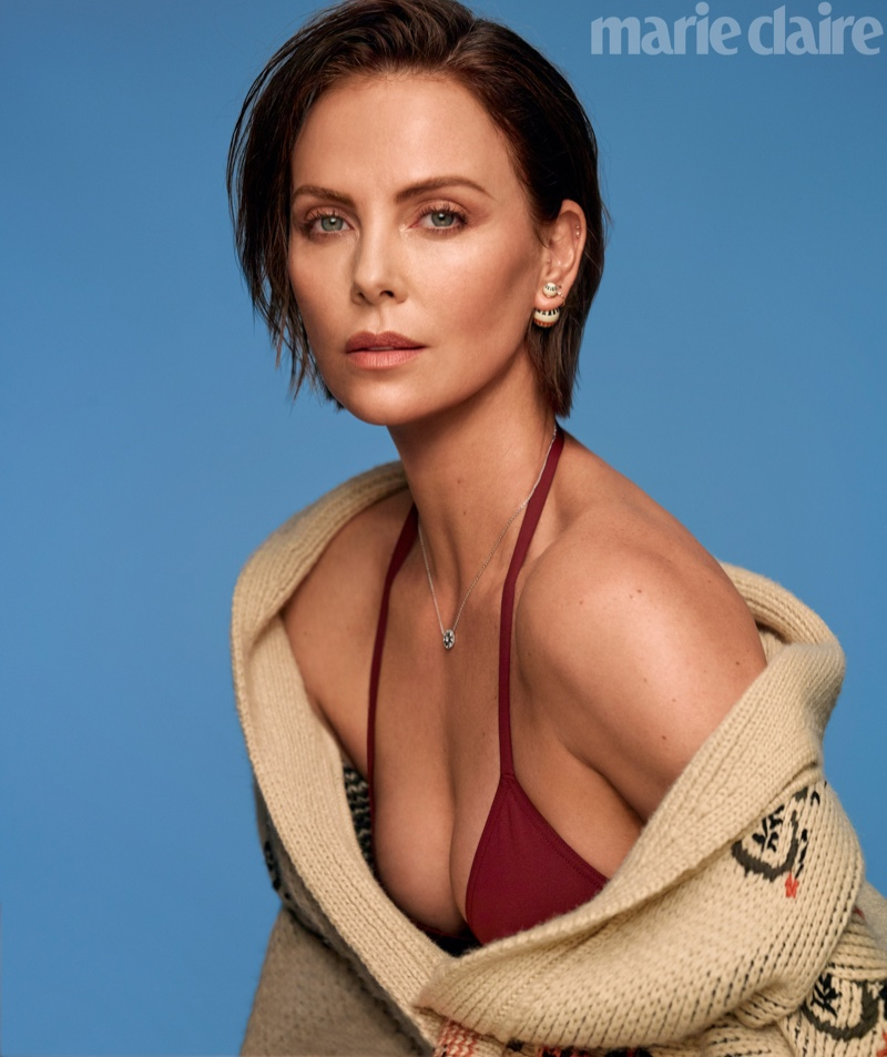 Actress Charlize Theron poses in Dior sweater, top, earrings and necklace