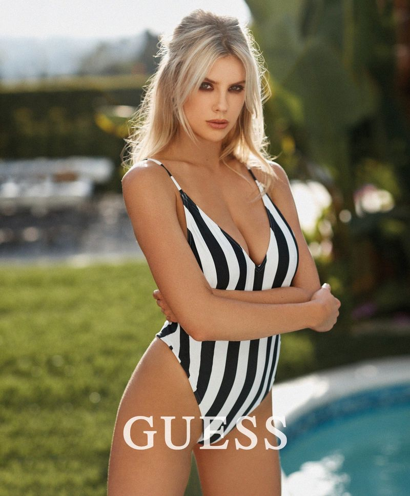 Wearing a striped swimsuit, Charlotte McKinney poses in design from Guess collaboration