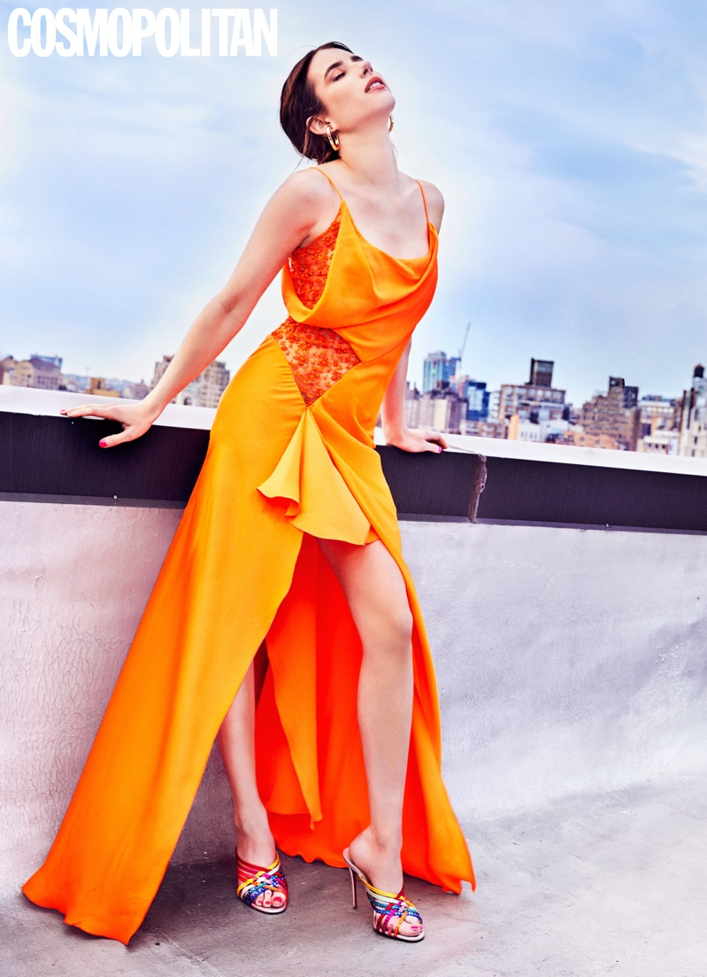 Emma Roberts poses in orange gown