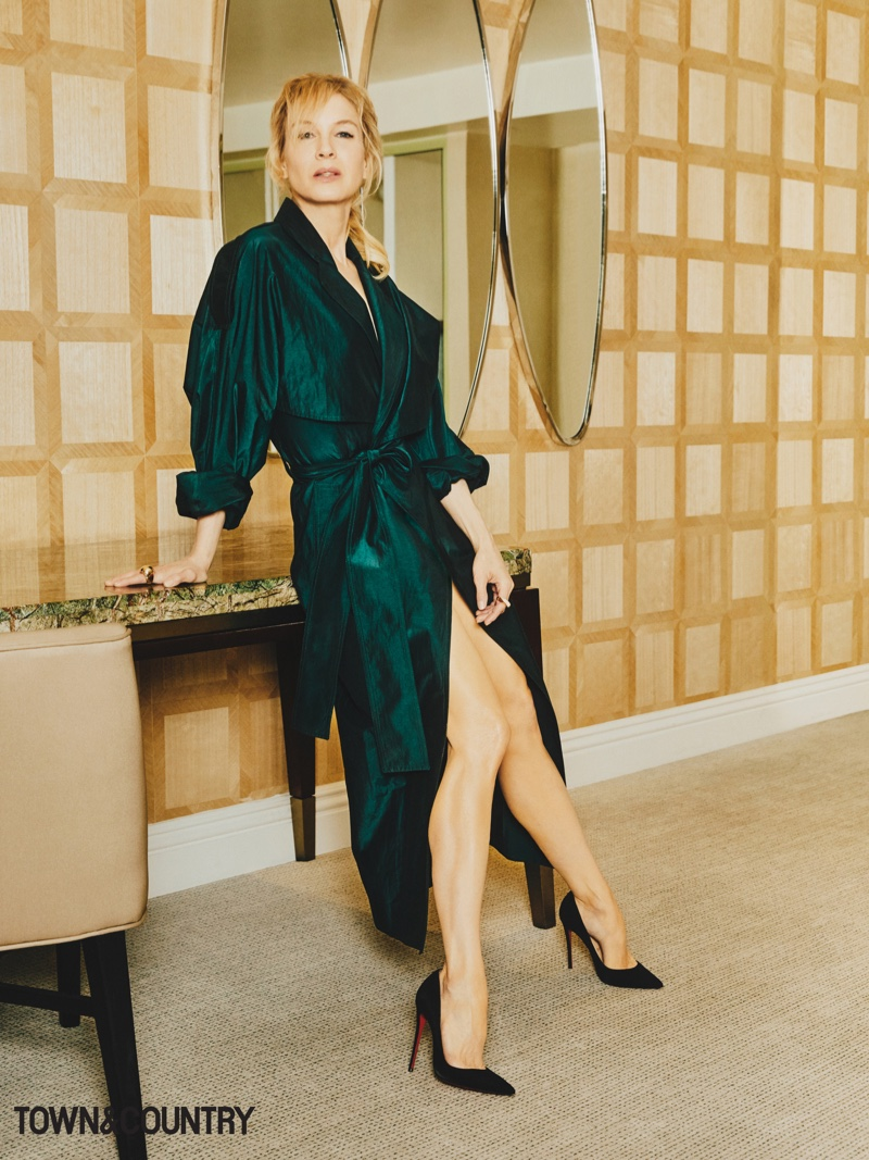 Renee Zellweger poses in Victoria Beckham trench dress with Cartier rings and Christian Louboutin pumps