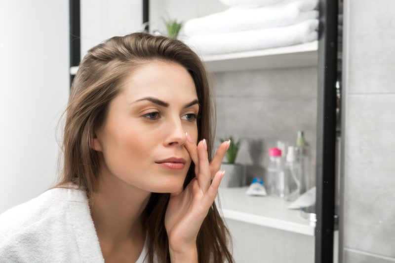 Woman Checking Face in Mirror